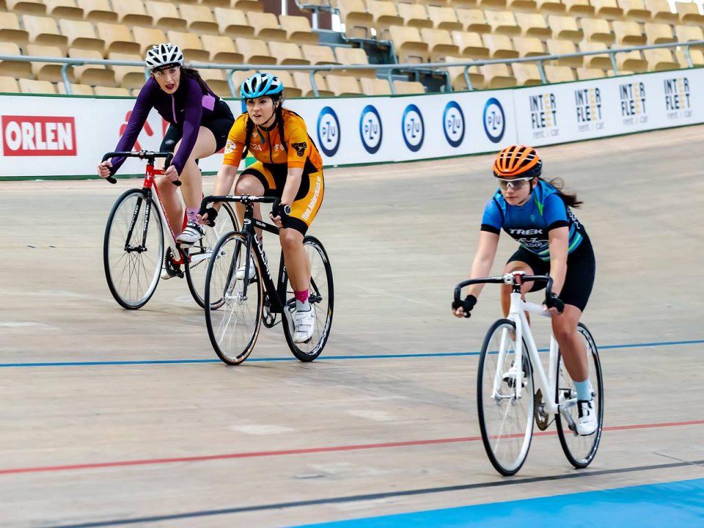 trzy kobiety jadące na rowerach po torze kolarskim.